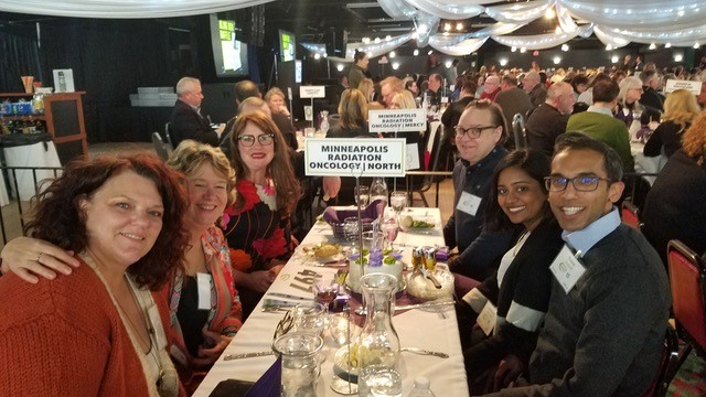 MRO staff around a dining table at a fundraising event.